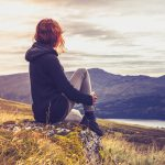 sad depressed woman sitting on hill