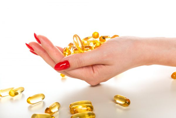 Vitamin Omega-3 fish oil capsules in a hand