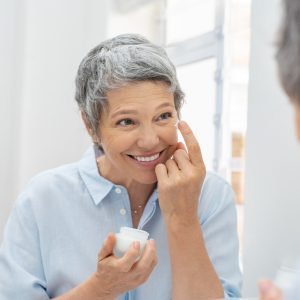 Happy mature woman applying face lotion anti aging skincare routine